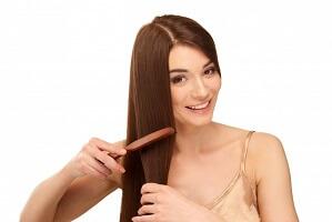 クシで髪をとかす女性