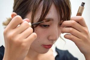 眉にマスカラを使う女性